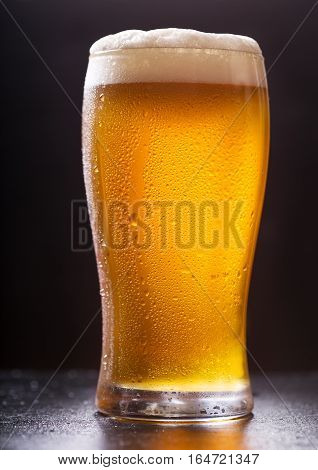 close up of glass of beer on dark background
