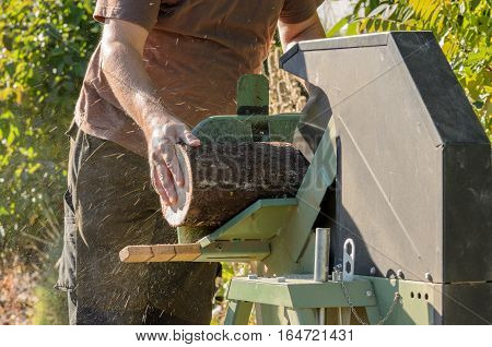 Man is using a electric saw for cutting firewood