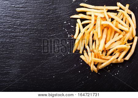 French fries potatoes on dark background, top view