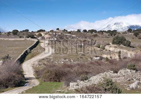 Dirt road in countryside of Madrid Spain. At the background snow capped peaks of the Guadarrama Mountains. Photo taken in Colmenar Viejo Madrid Province Spain