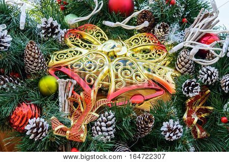 Large golden tracery plastic bells fir branches cones - festive decorations for the New Year Christmas. Decoration interior courtyard street. Close up