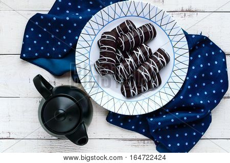 Fragrant cookies of choux pastry in dark chocolate covered with white decoration on a white plate and teapot on a wooden background. The top view