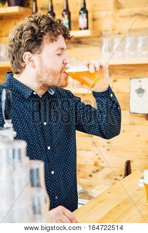 Side view of curly-haired man enjoying craft beer