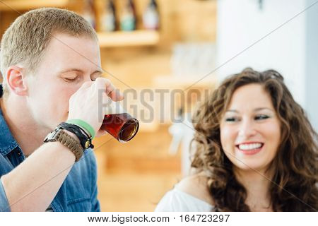 Portrait of blond man drinking craft beer with eyes closed.Smiling brunette near him.