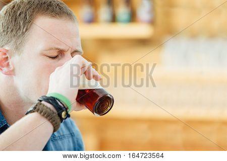 Portrait of blonde man with eyes closed enjoying dark craft beer