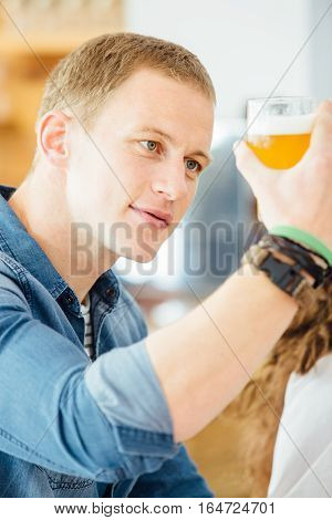 Handsome man looking at glass of light craft beer