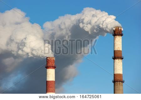 Dense clouds of smoke or steam out of two pipes on the background of blue sky. The concept of ecology pollution of the environment.