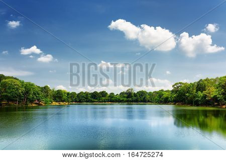Lake Nestled Among Rainforest In Cambodia Under Blue Sky