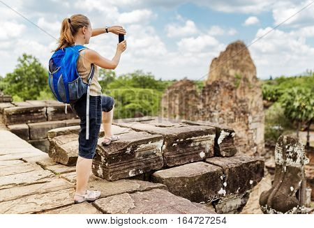 Tourist With Backpack Taking Picture In Angkor, Cambodia