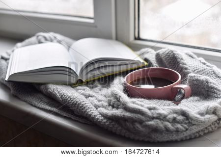 Cozy home still life: cup of hot coffee and opened book with warm plaid on windowsill against snow landscape outside. Winter holidays and Christmas time concept, free copy space.