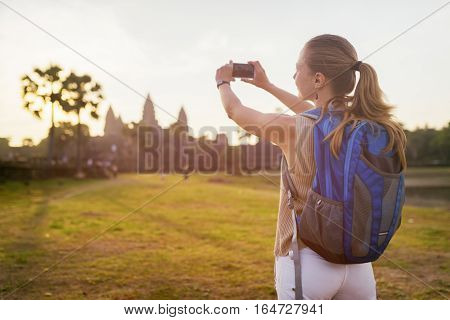 Young Female Tourist Taking Picture Of Angkor Wat In Cambodia