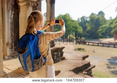 Young Female Tourist With Smartphone Taking Picture Of Angkor
