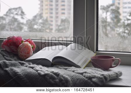 Cozy home still life: cup of hot coffee, spring flowers and opened book with warm plaid on windowsill against snow landscape outside. Springtime concept, free copy space.