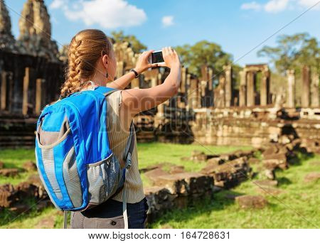 Young female tourist with blue backpack and smartphone taking picture among mysterious ruins of ancient Bayon temple in Angkor Thom in evening sun. Siem Reap Cambodia.
