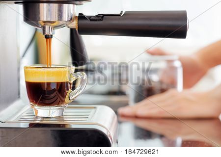 Espresso Coffee Machine In Kitchen. Coffee Pouring Into Cup