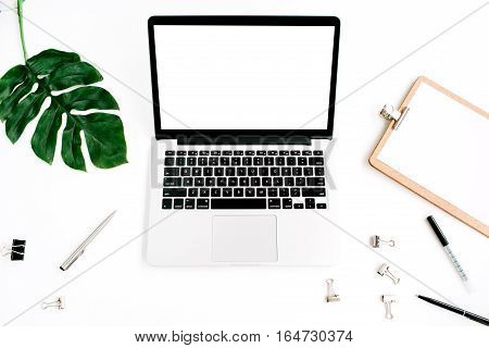Home office workspace mockup. Laptop with blank screen clipboard palm leaf and accessories. Flat lay top view