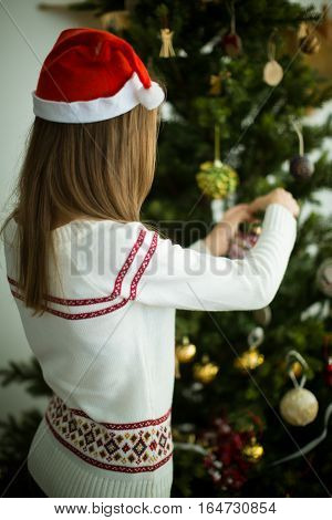 Rear view of young brunette girl in red cap decorates christmas tree with balls
