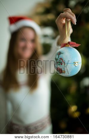 Close up of blue decorated christmas ball. Blurred woman on background.