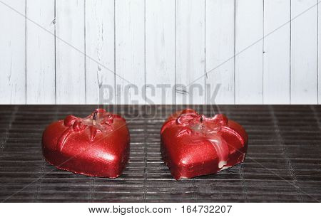Two candles in the shape of a heart on black and white background