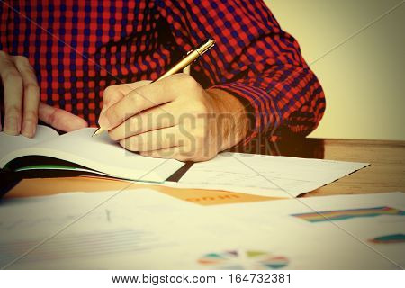 Close Up Left Hand Of Young Man Writing And Thinking About Cost At Home.