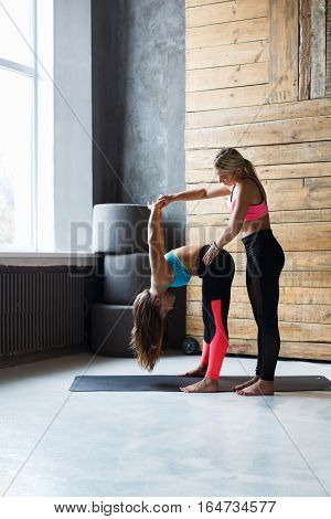 Yoga class instructor helps beginner to make asana exercises. Teacher assists to make standing forward bend pose. Healthy lifestyle in fitness club. Stretching with coach