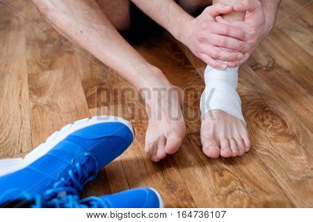 Sportsman Massaging His Injured Ankle