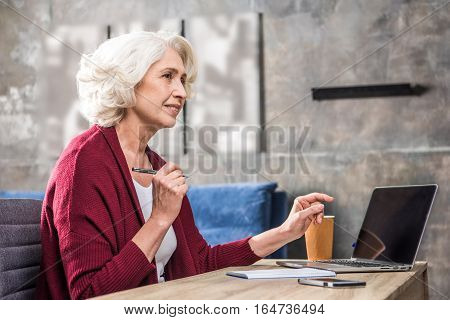 Attractive smiling senior woman freelancer holding pen sitting at the table with laptop