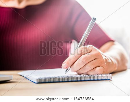 Woman Writing In Notebook