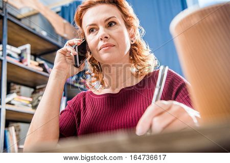 Attractive woman talking on smartphone and holding pen