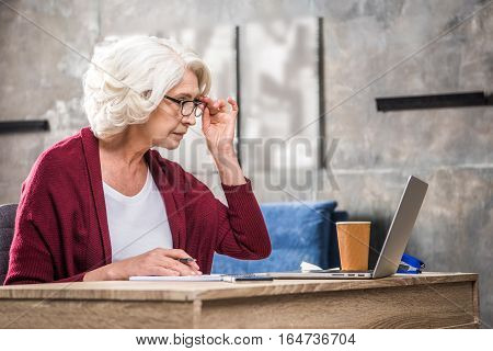 Senior Woman Adjusting Eyeglasses