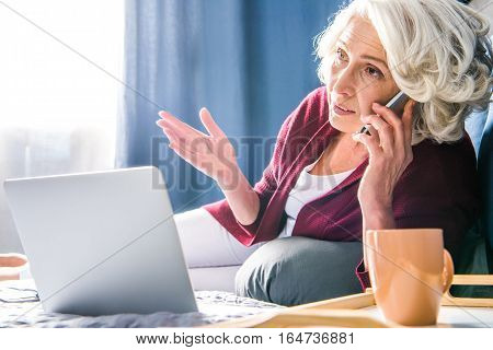 Attractive senior woman talking on smartphone while lying on bed