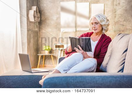 Senior woman sitting on sofa and making notes in notebook