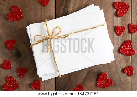 Stack Of Envelopes Tied With Twine Bow Surrounded By Heart Shapes On Wood Background