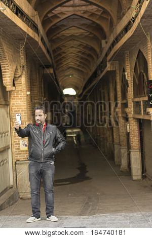 Tehran IRAN - January 6 2017 Taking a Selfie In Front of Tehran Old Covered Bazaar Passage by Cell Phone