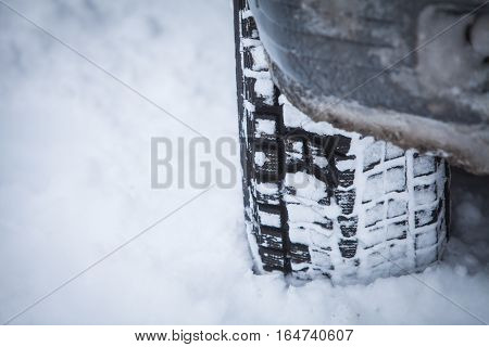 Close up shot of a car's winter tire in snow.