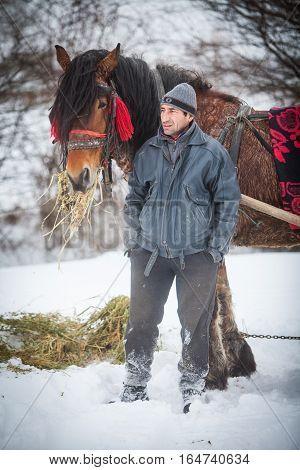 Pietrosani Romania - January 6 2017: A man stands near a horse in Pietrosani Romania.