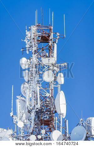 Telecommunication tower with dish and mobile antenna coverd by snow over blue sky.