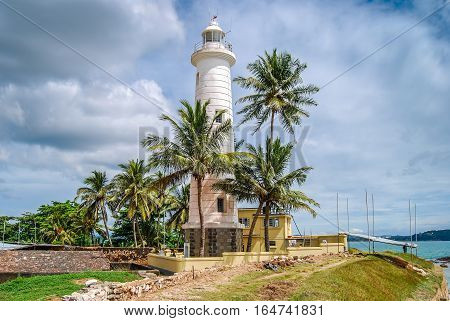 Lighthouse in Galle fort Sri Lanka. Indian ocean shore palms blue cloudy sky.