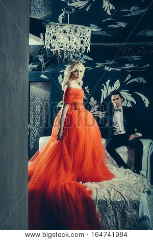 young handsome man in black suit and bow with pretty sexy women in red elegant evening dress with skirt and long curly hair with crown