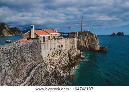 Coast venetian fortress Castello in Petrovac, Montenegro. Popular tourist attraction in Petrovac and Adriatic sea by evening. poster