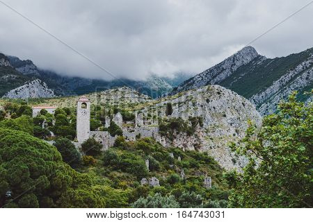 Ancient stone ruins and clock tower at Old Bar town on the cloudy mountains landsape, Montenegro. Stari Bar - ruined medieval city on Adriatic coast, Unesco World Heritage Site.