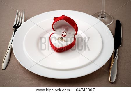 Golden Ring In Red Case On White Plate With Fork, Knife And Glass.