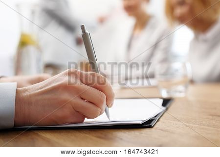 Signing of the contract. The woman signs a document