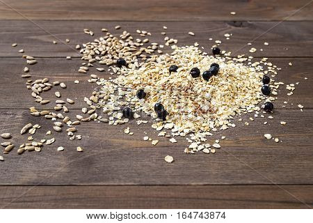 Muesli. Rolled oats sunflower and flax seeds and blueberries on a dark brown wooden background.