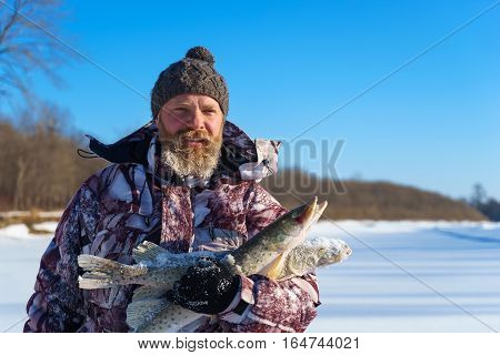 Bearded man is holding frozen fish after successful winter fishing at cold sunny day under clear blue sky