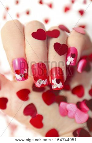 Nail designs with different sequins in the shape of hearts on red and pink nails for girls.