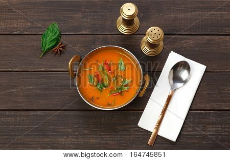 Vegan and vegetarian dish, spicy creamy tomato dahl soup bowl. Indian cuisine, masala hot meal on wood background. Eastern local cuisine restaurant food top view