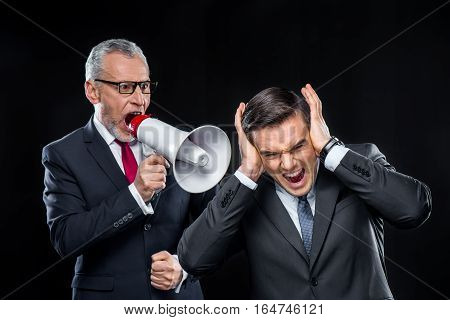 Mature businessman with loudspeaker shouting at his colleague