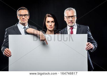 Three confident businespeople holding blank card on black