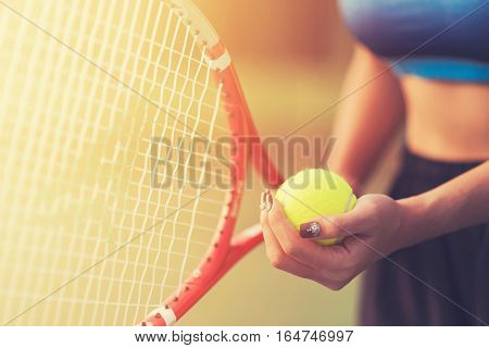 Player's hand with tennis ball preparing to serve in tennis cort. tennis ball on hand. tennis ball on sunset. tennis sport girl. tennis ball and racket. tennis player vintage tone.